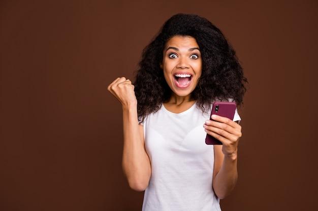 Retrato de niña afroamericana sorprendida conmocionada usa teléfono inteligente leer ganar lotería noticias de la red social impresionado grito wow omg use camiseta blanca.