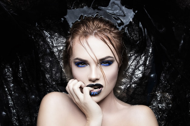 Retrato de una niña en el agua con un creativo color azul de las pestañas y los labios.