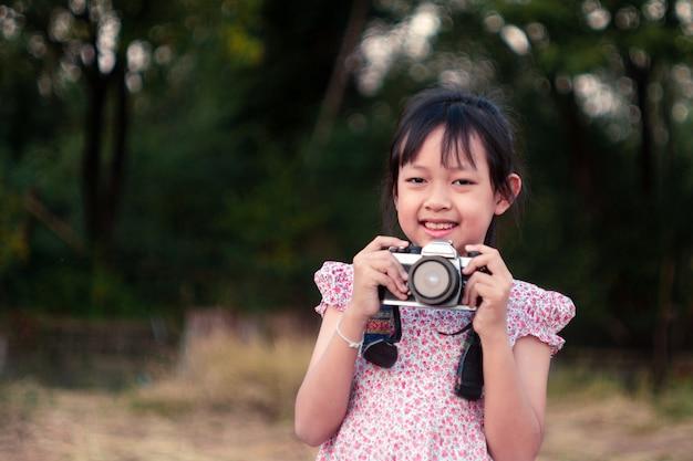 Retrato de niña alegre asiática tomando fotos con cámara de cine