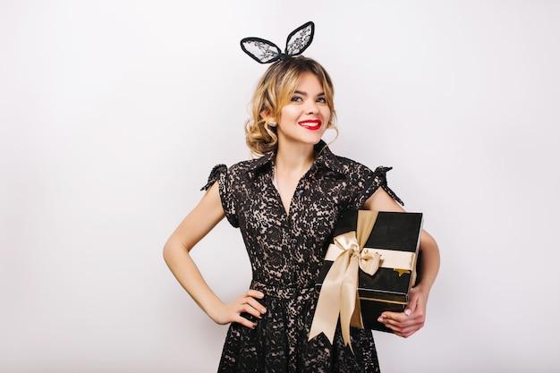 Retrato de niña alegre con cabello largo y rizado morena, vestido negro de lujo. celebrando, fiesta de cumpleaños, divirtiéndose con caja de regalo.