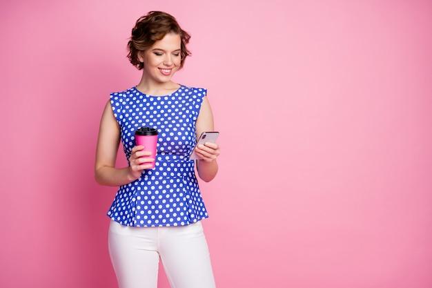 Retrato de niña alegre enfocada bebiendo café con leche charlando teléfono en línea