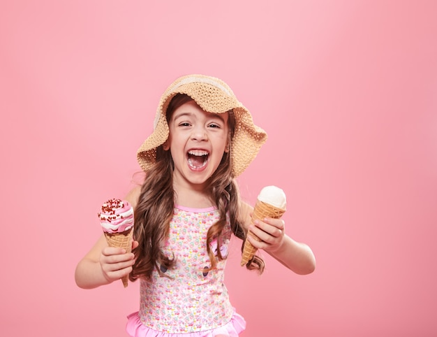 Retrato de una niña alegre con helado sobre un fondo coloreado
