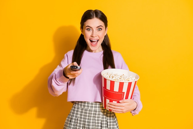 Retrato niña alegre listo ver tv interruptor control remoto mantenga palomitas de maíz