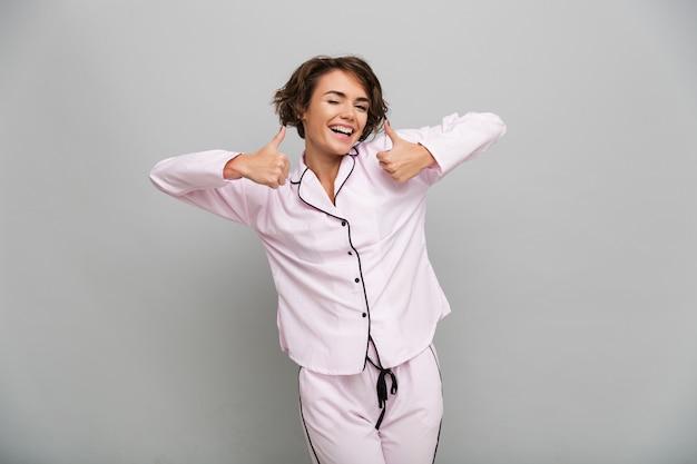 Retrato de una niña alegre en pijama mostrando los pulgares para arriba