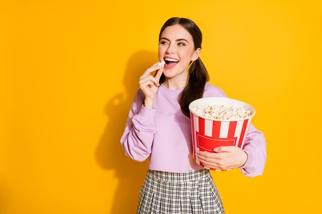 Retrato de niña alegre positiva disfrutar viendo cine comer palomitas de maíz