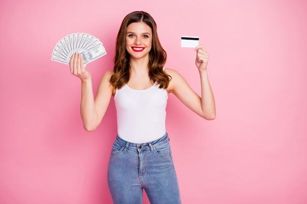 Retrato de niña alegre positiva mantenga dinero ventilador recomendar tarjeta de débito