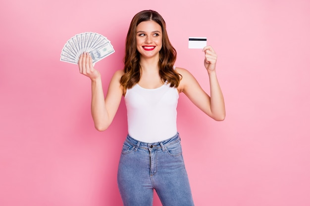 Retrato de niña alegre positiva mantenga la tarjeta de débito del ventilador de dinero