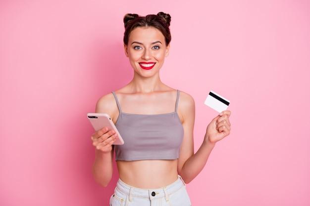 Retrato de niña alegre positiva usa smartphone paga sus compras en línea que paga con tarjeta de débito usa ropa gris de verano con estilo moderno aislada sobre color rosa