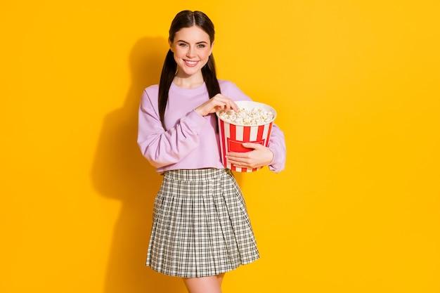 Retrato de niña alegre positiva ver series interesantes comer palomitas de maíz