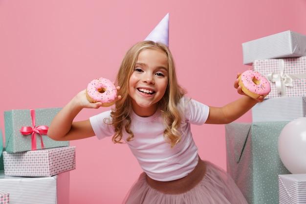 Retrato de una niña alegre en un sombrero de cumpleaños