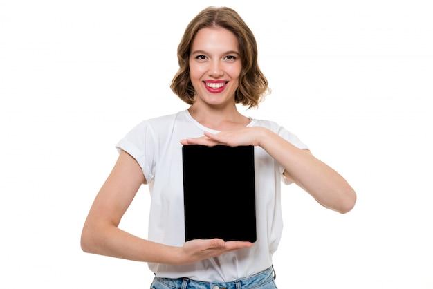 Retrato de una niña alegre sonriente mostrando tableta de pantalla en blanco