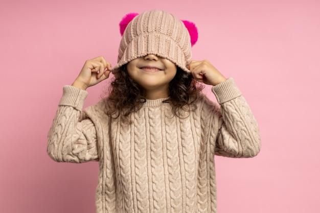 Retrato de niña alegre con suéter beige, divirtiéndose, tapándose los ojos con gorro de punto, sonriendo, riendo aislado. invierno, sombrerería, moda.