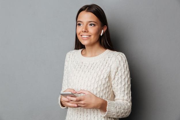 Retrato de una niña alegre en suéter escuchando música