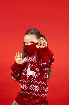 Retrato de niña alegre en suéter rojo de navidad con renos y con cuello en media cara mostrando ...