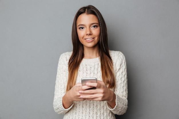 Retrato de una niña alegre en suéter con teléfono móvil