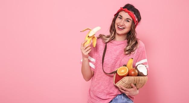 Retrato de una niña con alimentos saludables, frutas, en una pared rosa