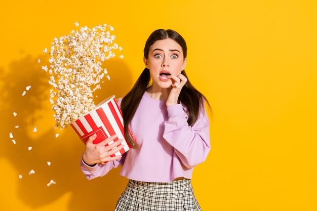 Retrato de niña ansiosa ver película de terror dientes dedo sujetar caja grande palomitas de maíz