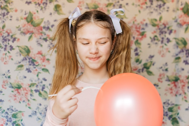 Retrato de una niña apareciendo globo con tenedor