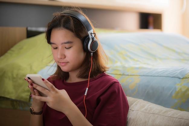 Retrato de niña asiática feliz escuchando música con auriculares