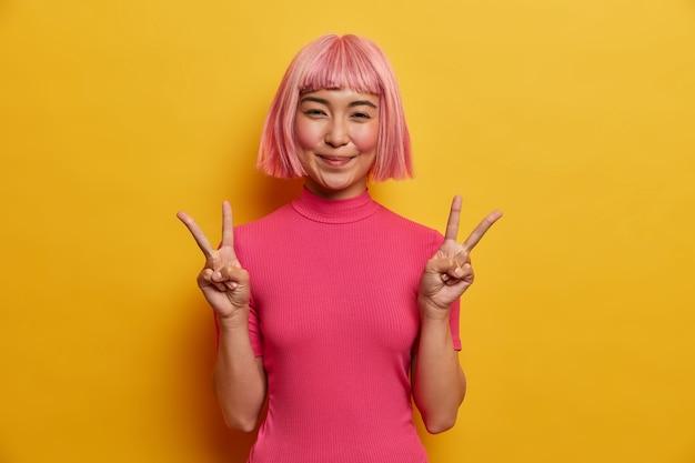 Retrato de niña asiática feliz hace el signo de la paz, hace el signo de la victoria, cree en ganar, se regocija en el éxito