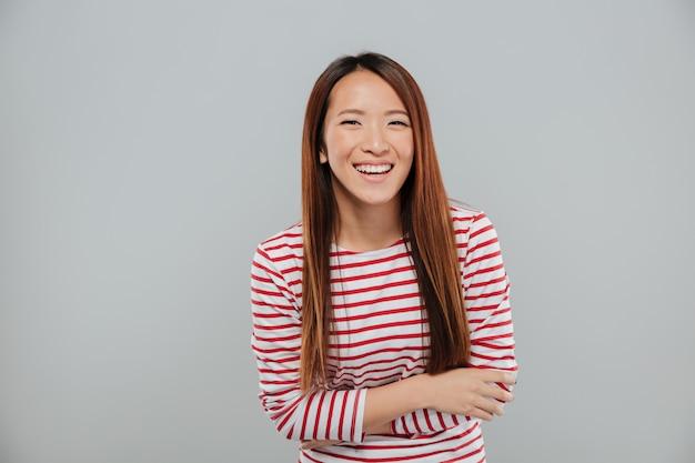Retrato de una niña asiática feliz riendo mientras está de pie