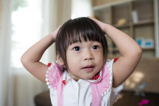 Retrato de niña asiática jugando en su casa