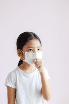 Retrato de niña asiática lleva una mascarilla sanitaria y tos. la epidemia de gripe, coronavirus o covid-19 y enfermedad con smog.