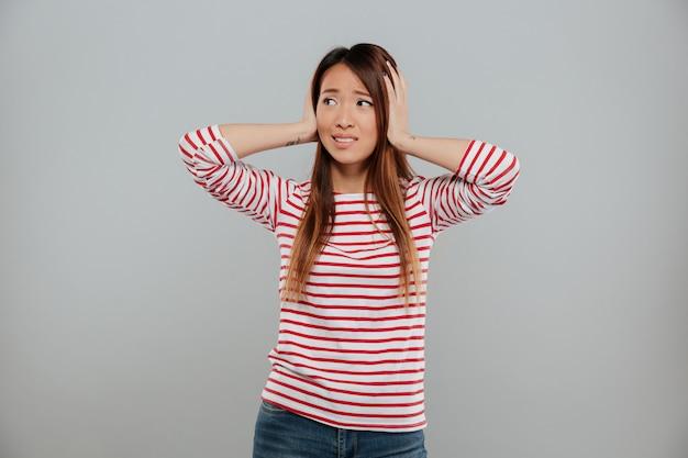 Retrato de una niña asiática perpleja de pie con las manos