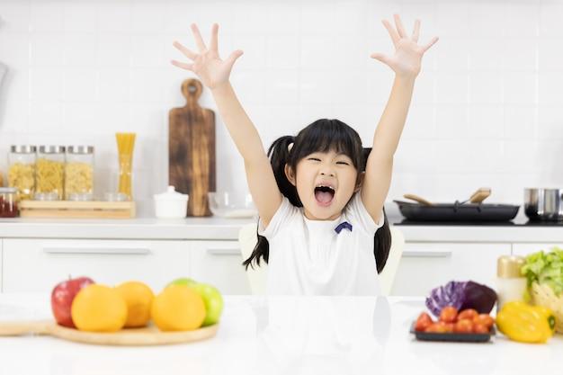 Retrato de niña asiática sonriendo en la cocina