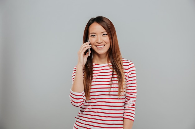 Retrato de una niña asiática sonriente hablando por teléfono móvil