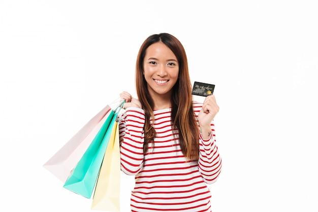 Retrato de una niña asiática sonriente sosteniendo bolsas de compras