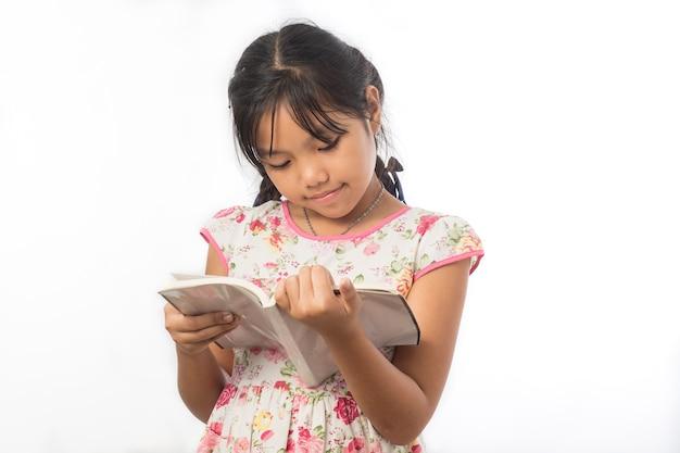 Retrato de niña asiática sosteniendo un libro sobre blanco