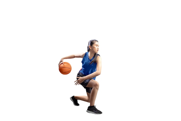 Retrato de niña asiática en uniforme deportivo azul en movimientos de pivote de baloncesto