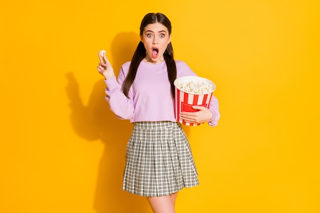 Retrato de niña asombrada mira la serie de terror de televisión impresionado wow come grandes palomitas de maíz