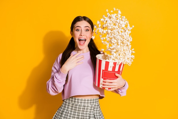 Retrato de niña asombrada ver serie increíble mantenga caja grande pop corn fly