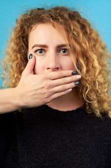 Retrato de niña atractiva rizada pelirroja asustada cubriendo su boca con su mano