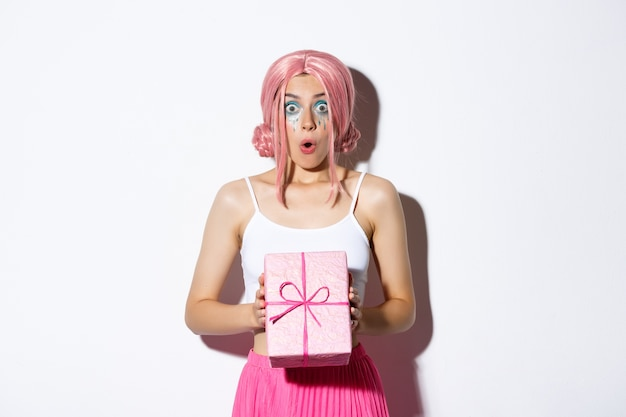Retrato de niña atractiva sorprendida que parece emocionada, recibe un regalo de cumpleaños, con peluca rosa, de pie.