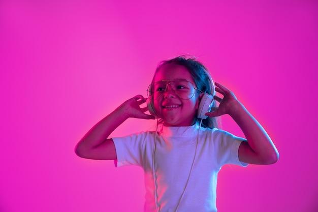 Retrato de niña en auriculares en la pared de neón púrpura