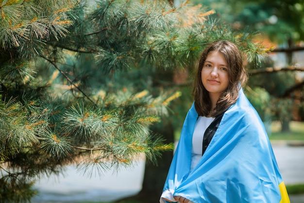 Retrato de niña con bandera nacional ucraniana en el parque al aire libre