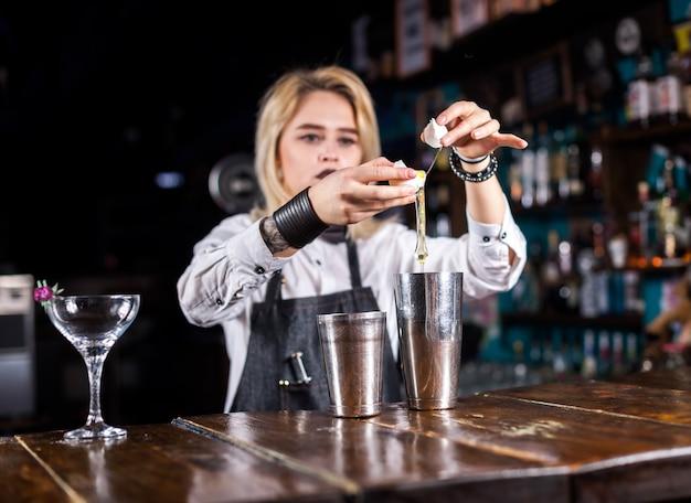Retrato de niña barman demuestra el proceso de elaboración de un cóctel en el bar