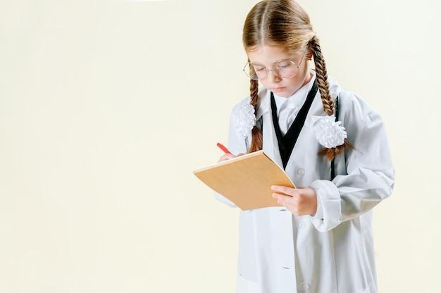 Retrato de una niña en una bata blanca con gafas, documentos y un estetoscopio que mira a la cámara y sonríe