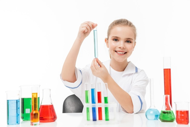Retrato de niña en bata blanca de laboratorio haciendo experimentos químicos con líquido multicolor en tubos de ensayo aislado sobre pared blanca