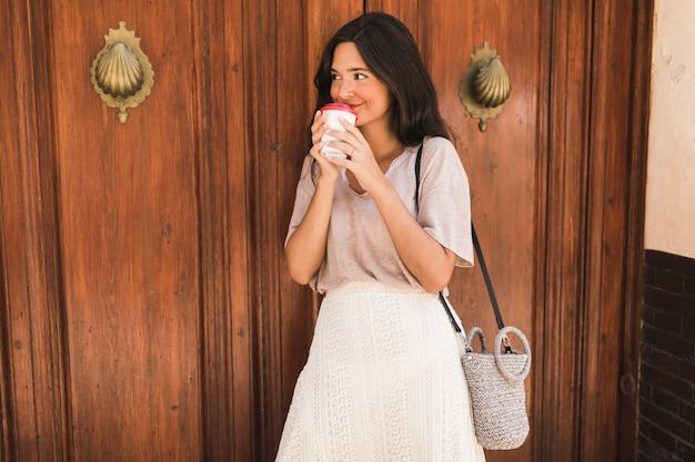 Retrato de una niña bebiendo café de una taza desechable