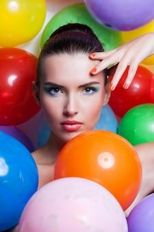 Retrato de niña de belleza con maquillaje colorido, esmalte de uñas y accesorios. estudio colorido tirado de mujer divertida.