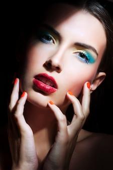 Retrato de niña de belleza con maquillaje colorido