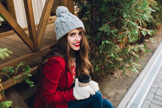 Retrato de niña bonita en abrigo rojo, gorro de punto sentado en escaleras de madera cerca de ramas verdes al aire libre. ella sostiene café con guantes blancos y sonriendo. vista desde arriba.