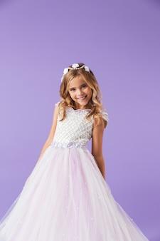 Retrato de una niña bonita alegre sonriente vestida con un vestido de princesa aislado sobre la pared violeta, bailando