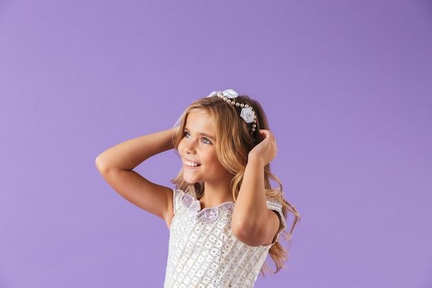 Retrato de una niña bonita alegre sonriente vestida con un vestido de princesa aislado sobre la pared violeta, mirando a otro lado