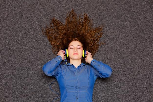 Retrato de una niña bonita en auriculares disfrutando de la música.