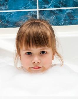 Retrato de niña bonita en el baño.